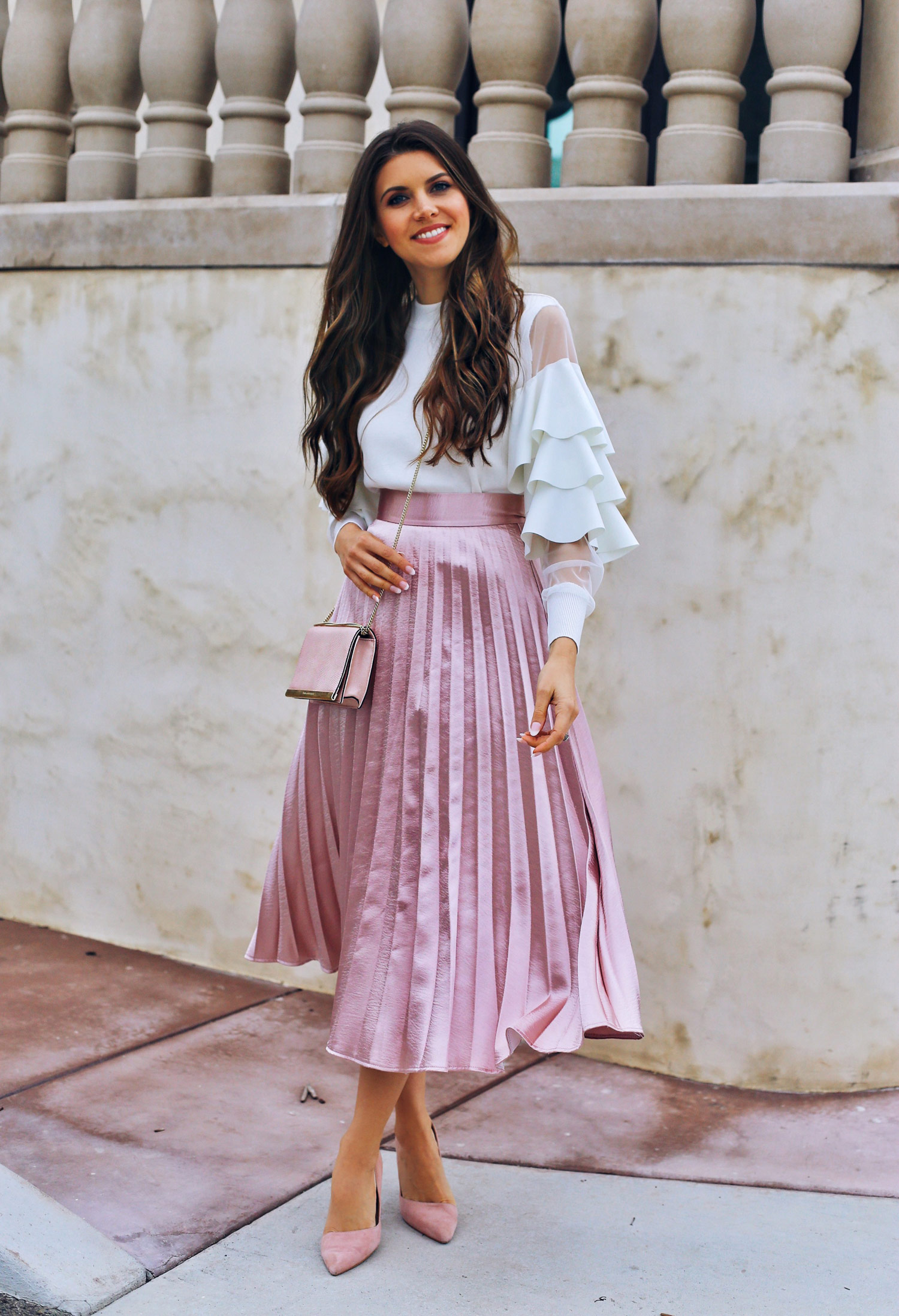 Fashion and lifestyle blogger Adelina Perrin of The Charming Olive wearing Chicwish tiered sleeve top and pink pleated skirt