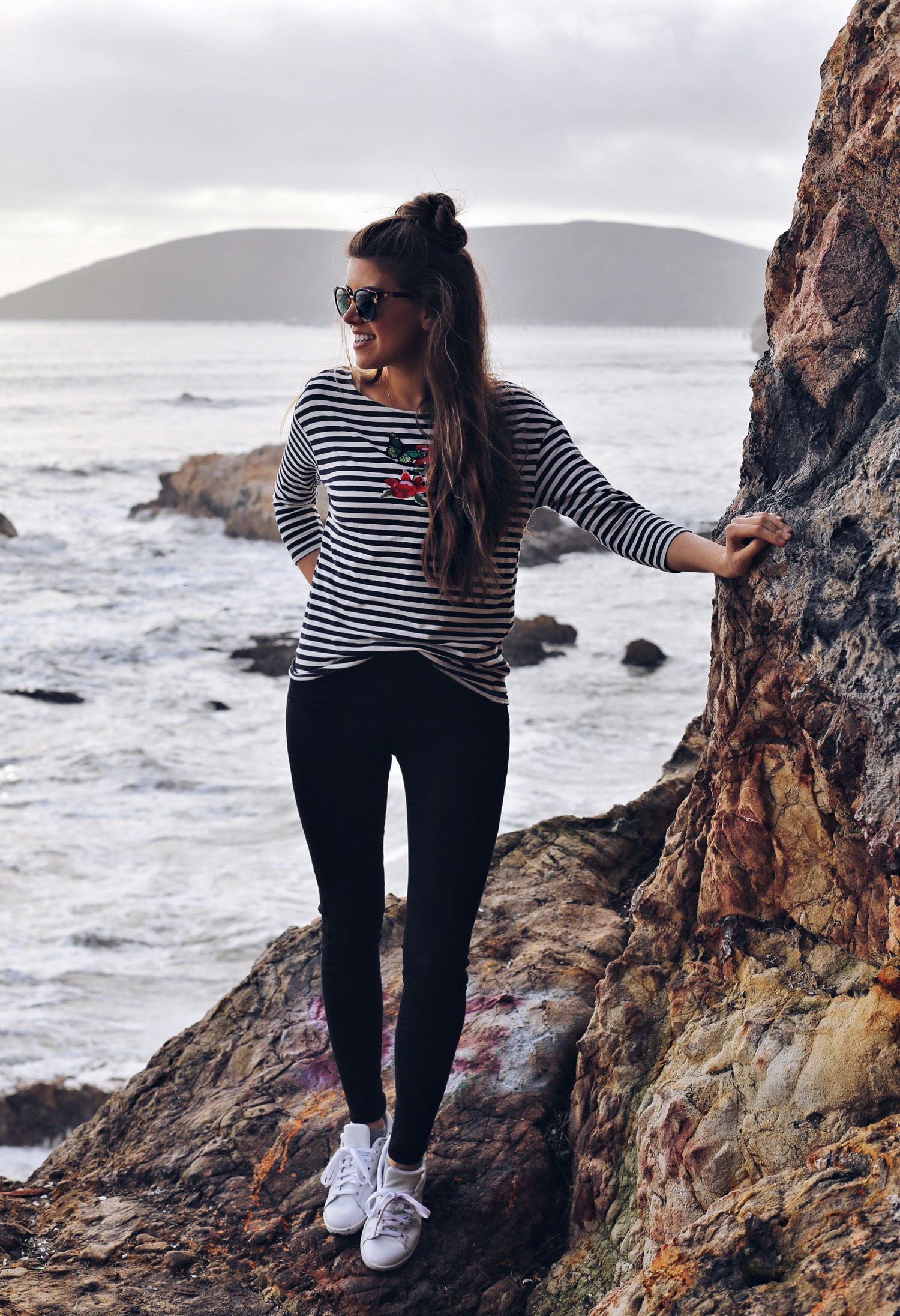 Fashion and lifestyle blogger Adelina Perrin of The Charming Olive wearing Marks & Spencer striped top, Mott & Bow Jeans, Adidas Sneakers and Tory Burch Sunglasses
