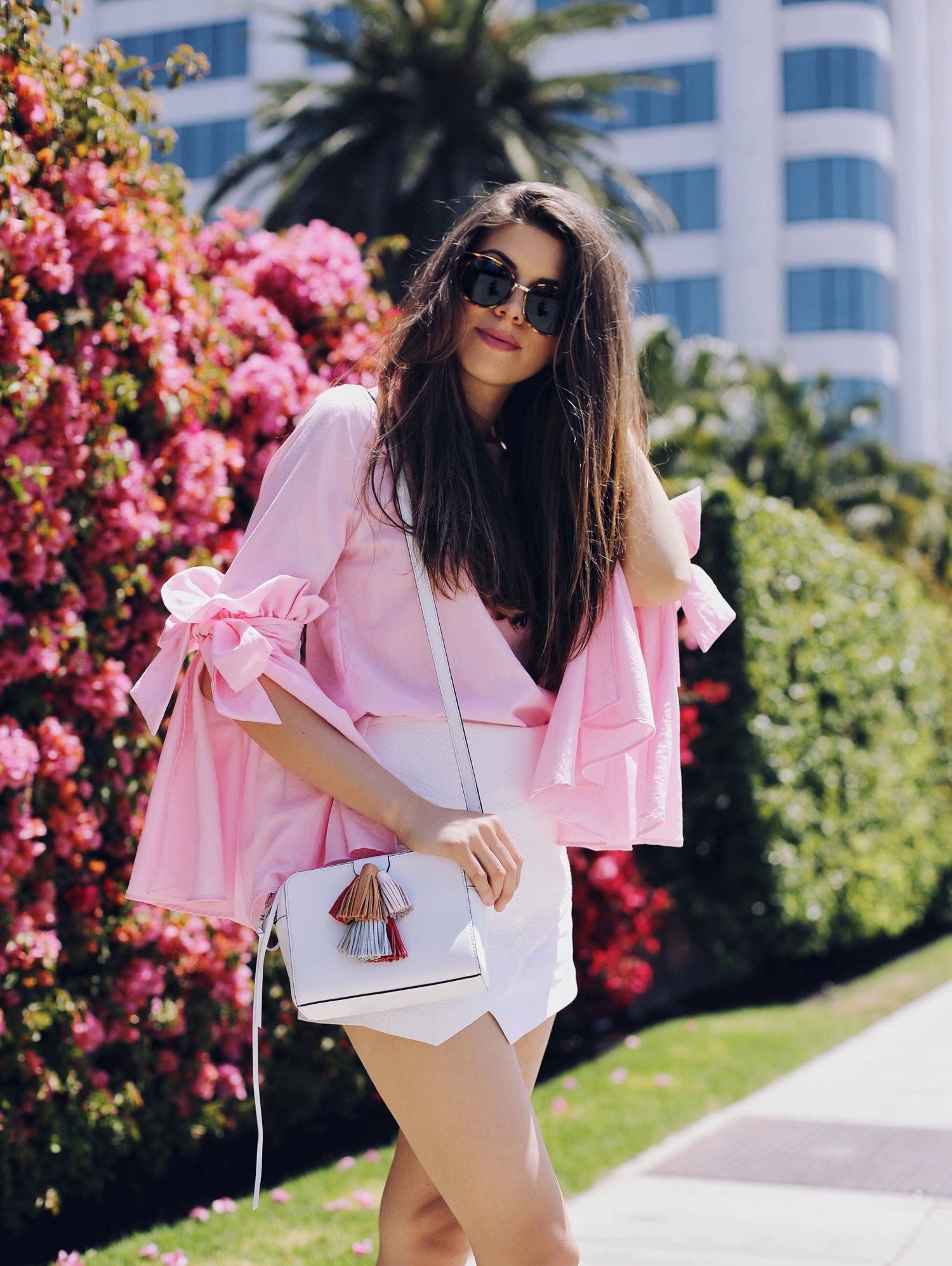 Fashion and lifestyle blogger Adelina Perrin of The Charming Olive wearing Chicwish Pink Top, Revolve White Skorts, Rebecca Minkoff bag