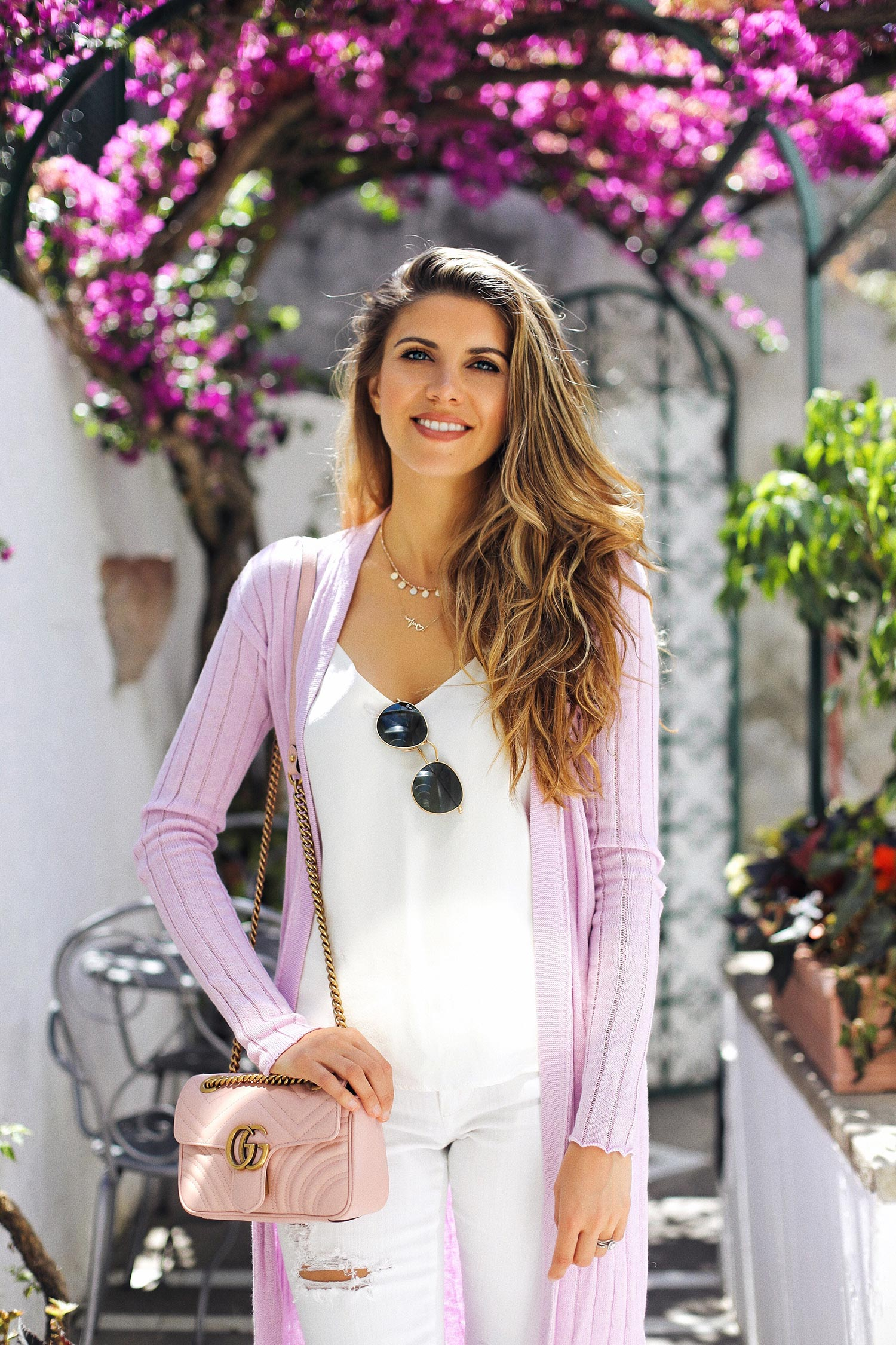 Fashion and lifestyle blogger Adelina Perrin of The Charming Olive sharing the best skincare for travel, wearing Gucci marmont bag, l'agence cami, lavender cardigan.