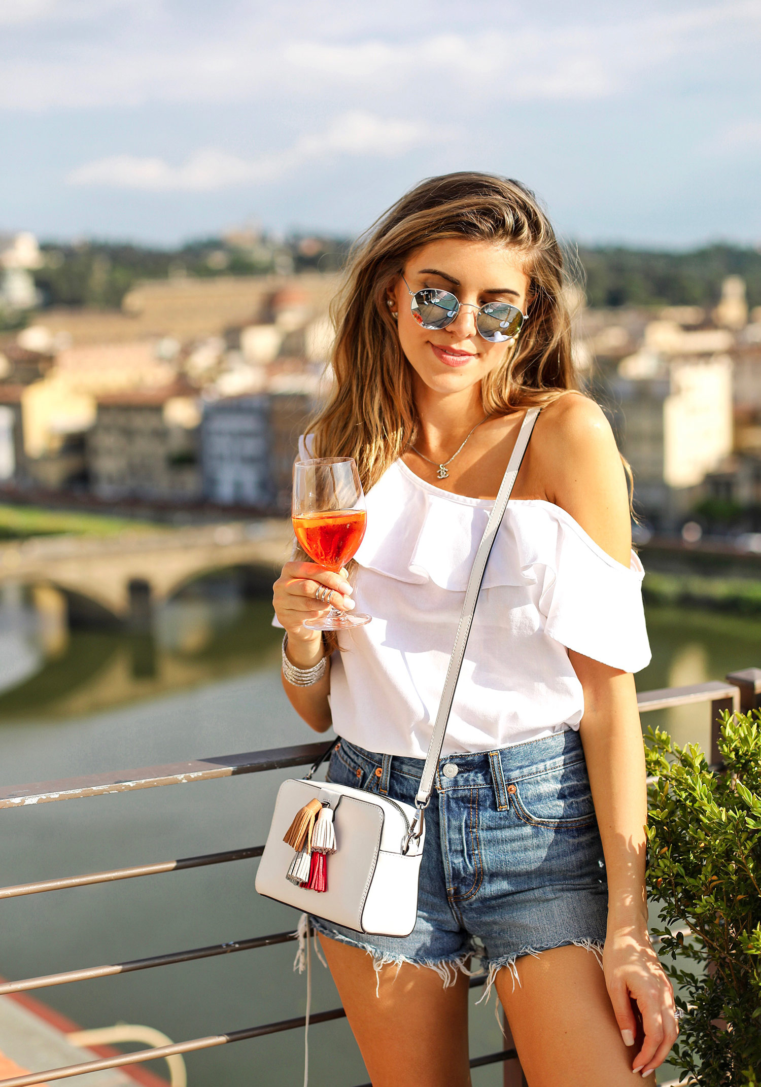 Fashion and lifestyle blogger Adelina Perrin of The Charming Olive wearing Madewell Top, Levis Shorts, and Rebecca Minkoff bag