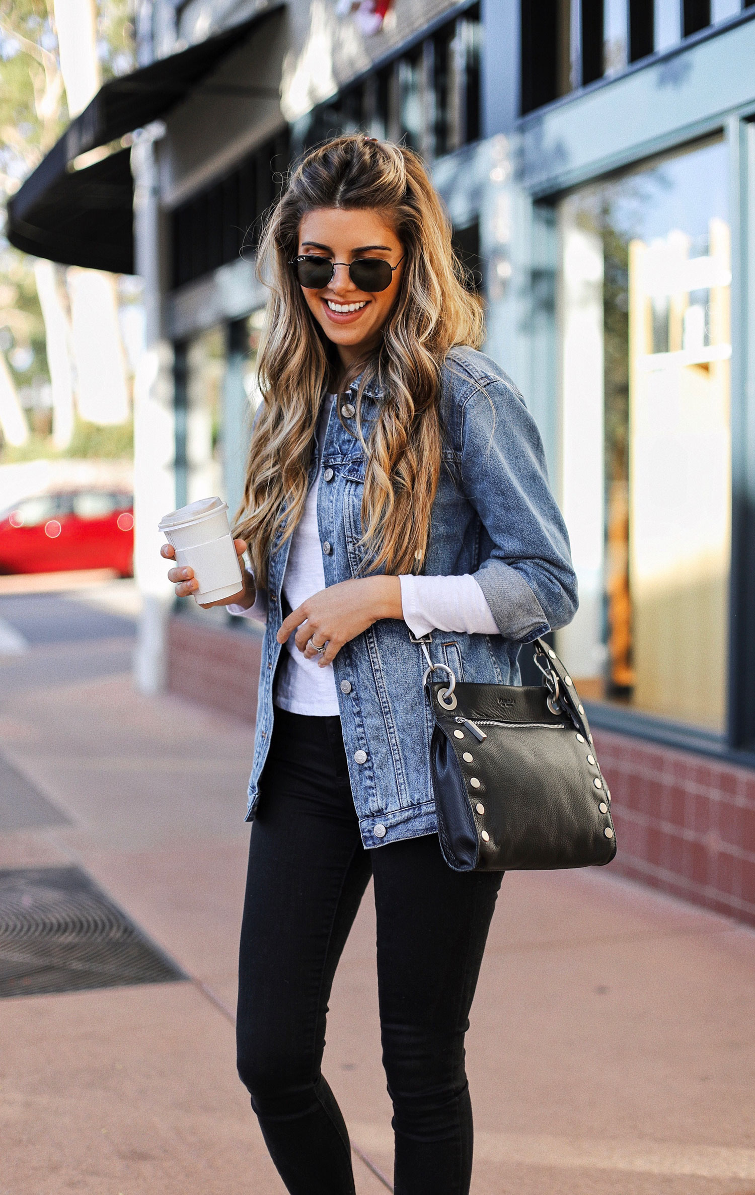 Fashion blogger Adelina Perrin of The Charming Olive wearing Madwell denim jacket and Hammitt LA cross body bag
